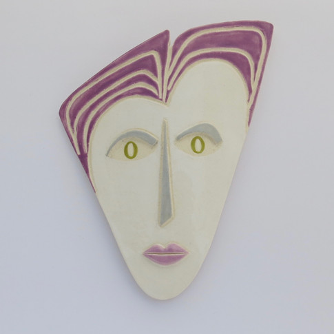 Curved earthenware ceramic face decorated with glazes.  Hanger on the back for wall mounting. 20cm x 16cm x 2cm