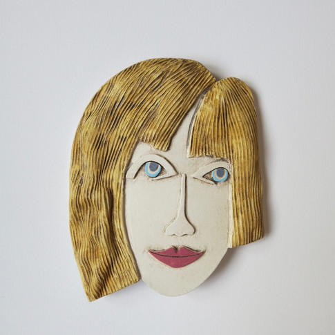 Curved earthenware ceramic face decorated with oxide and underglazes.  Hanger on the back for wall mounting. 18cm x 15cm x 2cm
