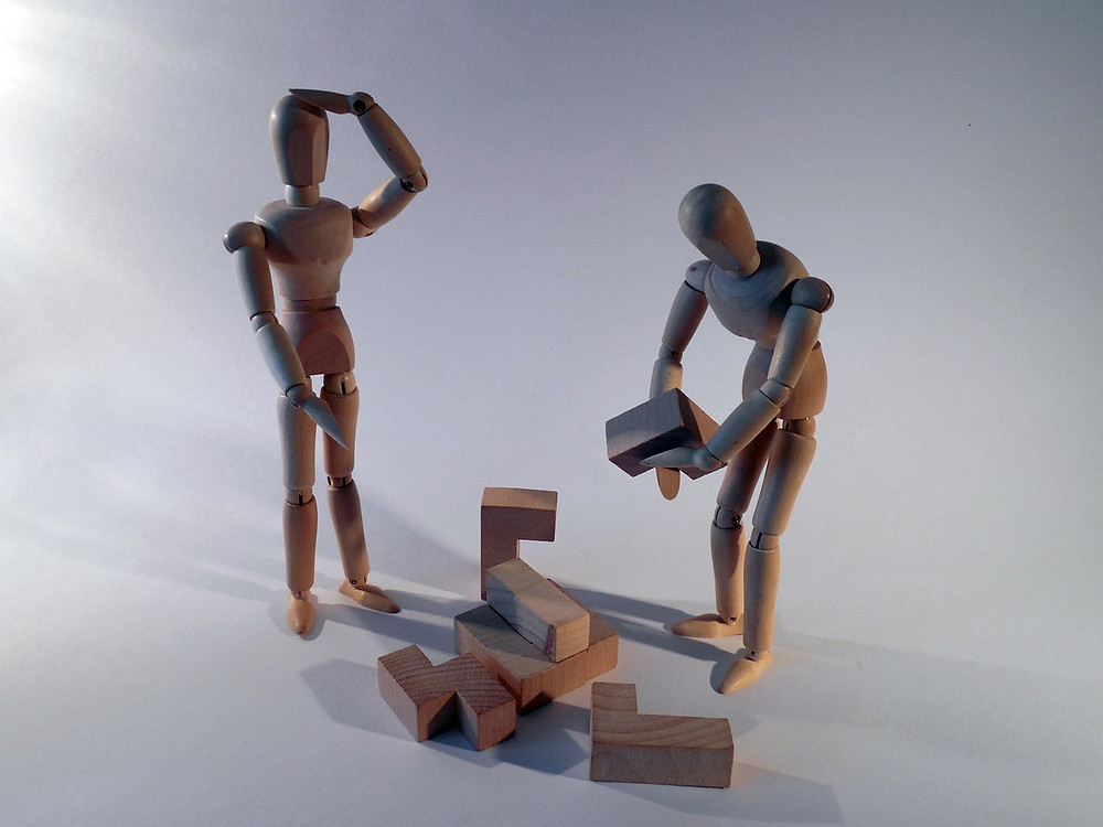 Photo of 2 wooden statues attempting to build a third out of pieces of wood