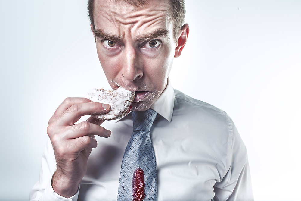 photo of man eating donut with jelly spilled on his tie