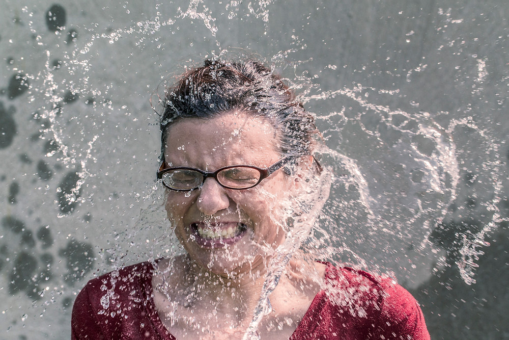 woman getting water splashed in her face