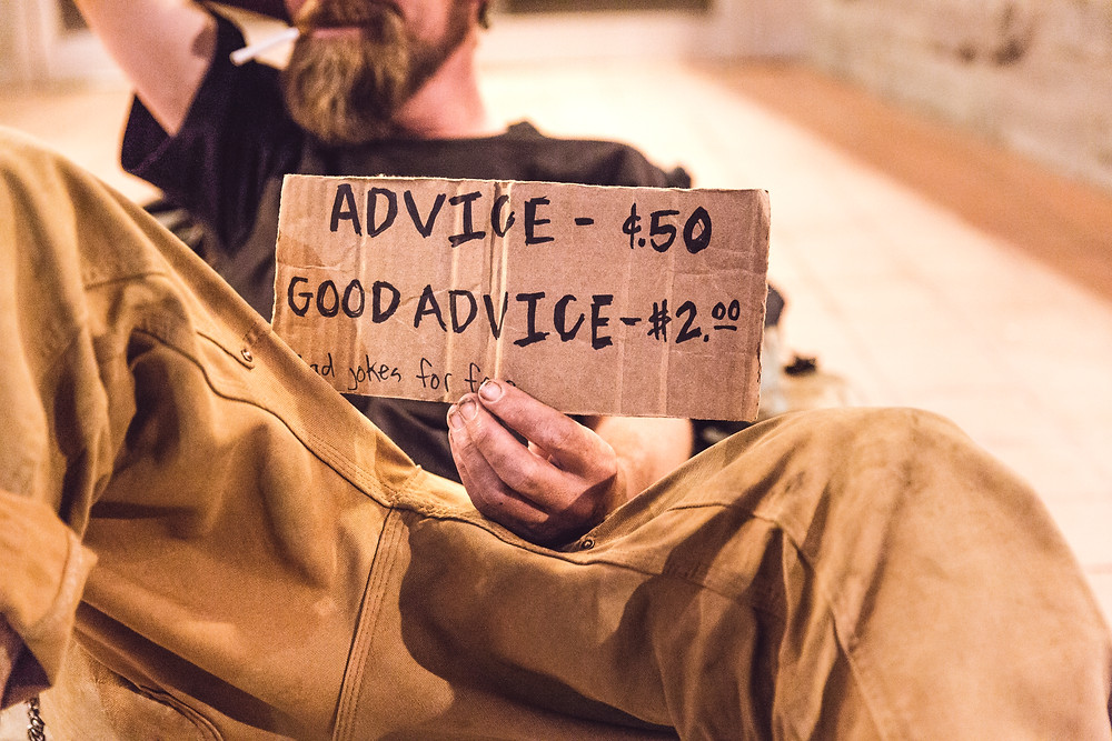"Image of man laying down holding sign ""advice - ¢.50, good advice - $2.00"""