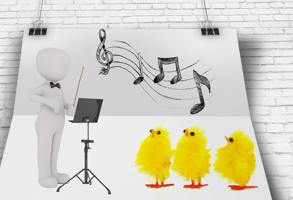 Image of stick figure with black tie, black wand in front of music stand with 3 yellow chicks and musical notes above them