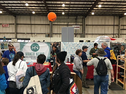 Maker Fair booth with volunteers and visitors talking about the hackerspace