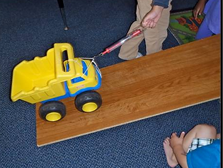 Student pulls toy truck up ramp to measure physics experiment