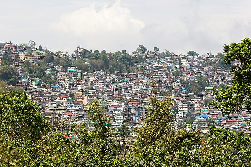 View of a town surrounded by trees and having colorful house structures