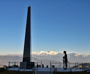 Man standing next to tall memorial with a view of the mountains