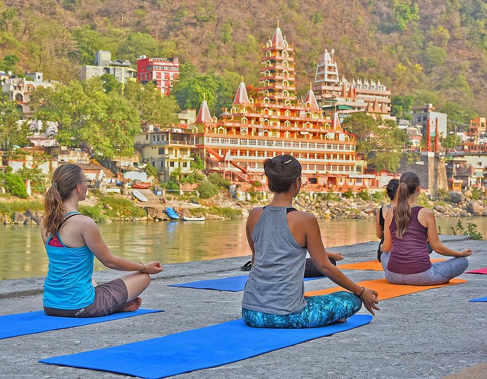Women performing yoga on mats beside a river near city dwellings