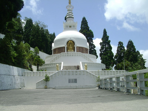 picture of a white pagoda structure with gold highlights and trees in the backdrop