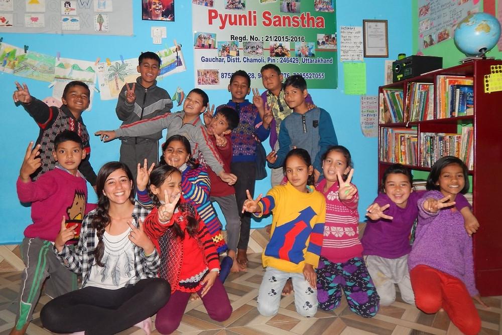 Volunteer women in a school surrounded by children