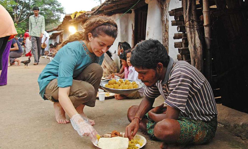 Volunteer crouching down to serve food to a local village resident in rural India