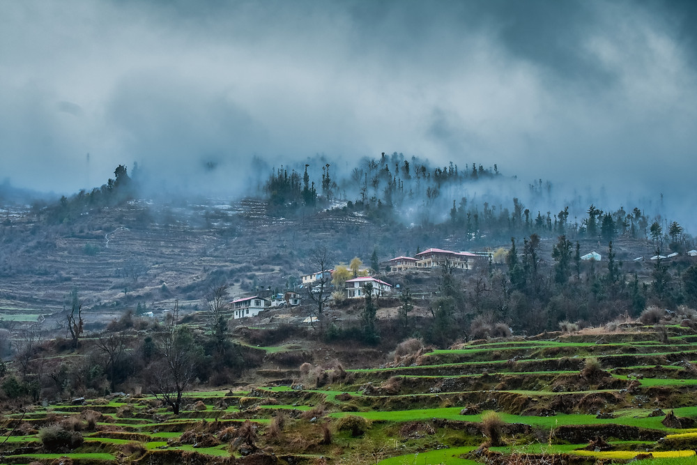 Steep mountain valleys and small village houses surrounded in green and fog