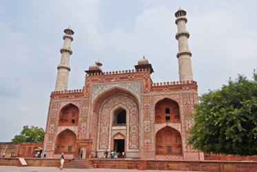 Red brick fortress structure with towers and white carvings