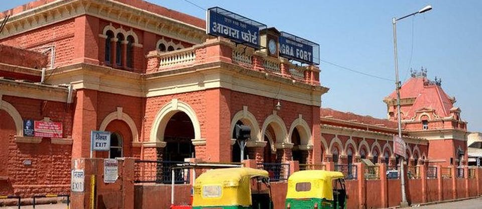 Red brick building with auto rikshaws outside