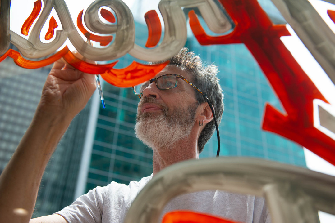 """Ted Penovich, of Wexford, paints the window of Pittsburgh Popcorn in Downtown on Friday, June 7, 2019. """"When people do it, it seems to catch your eye more, you see the imperfections,"""" he said. """"That's been my selling point for years, my work has a soul because I did it."""" He says he got into window shop painting by accident, now he's been doing it for 30 years. (Delia Johnson/Post-Gazette)"""
