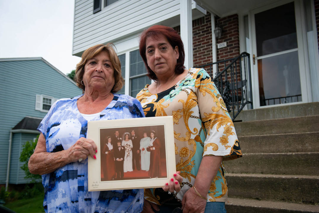 Michelle Vaglia, of Apollo, and Judy Poklemba, of Monroeville, pose for a portrait holding a photo from Vaglia's wedding at Poklemba's home on June 12, 2019, in Monroeville. The photo taken in March of 1973 is the last picture they have of the whole family together before their sister Janice Pietropola became one of two victims in a murder at Virginia Beach in June 1973. (Delia Johnson/Post-Gazette)