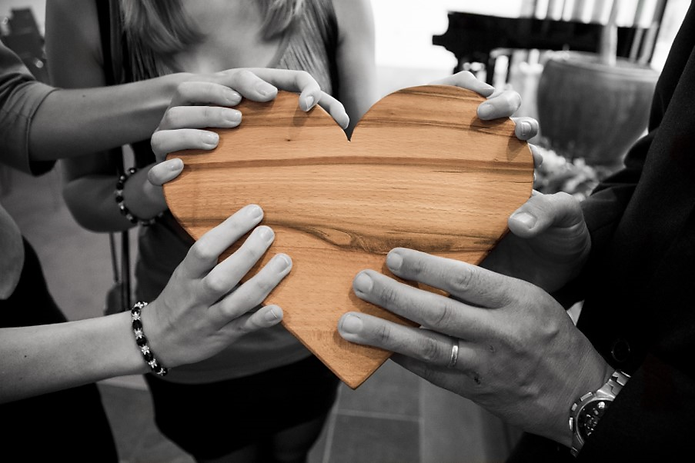 Hands holding a heart shaped piece of wood