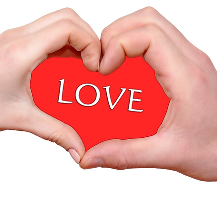 """Hands holding a red """"Love"""" heart"""