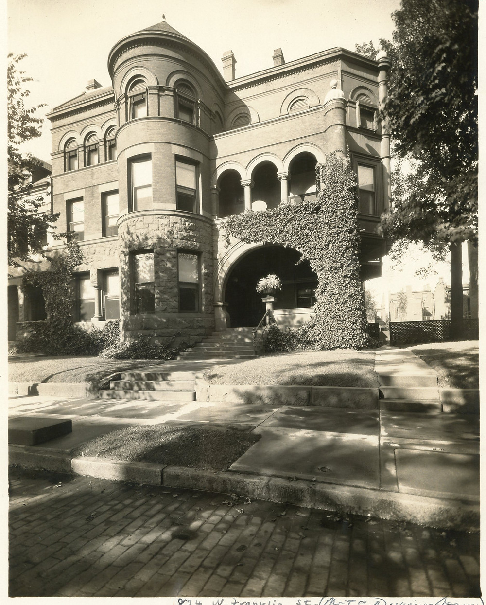 Black and white photograph of a three story masonry house with elaborate arches and ivy coverig part of the entrance.