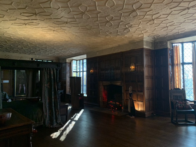 A large room with plaster ceilings with decorative geometric designs and dark wood panelling. Two windows frame a fireplace. There is a large bed draped in heavy fabric to the left in the image.