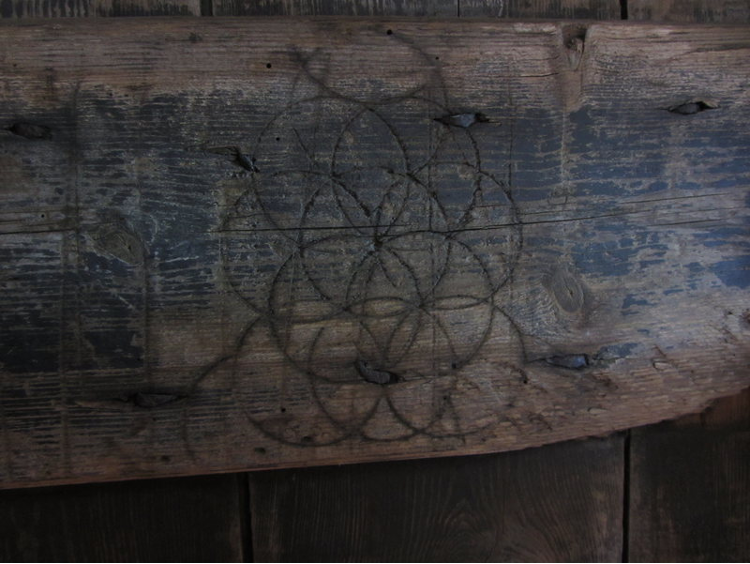 A detailed image of a worn wood panel with a series of carved, overlapping circles forming daisy patterns.