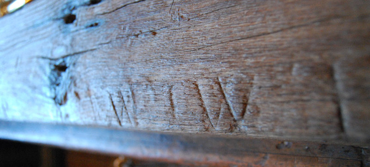 """Detail of plain wood molding with lightly carved lines resembling """"w"""""""