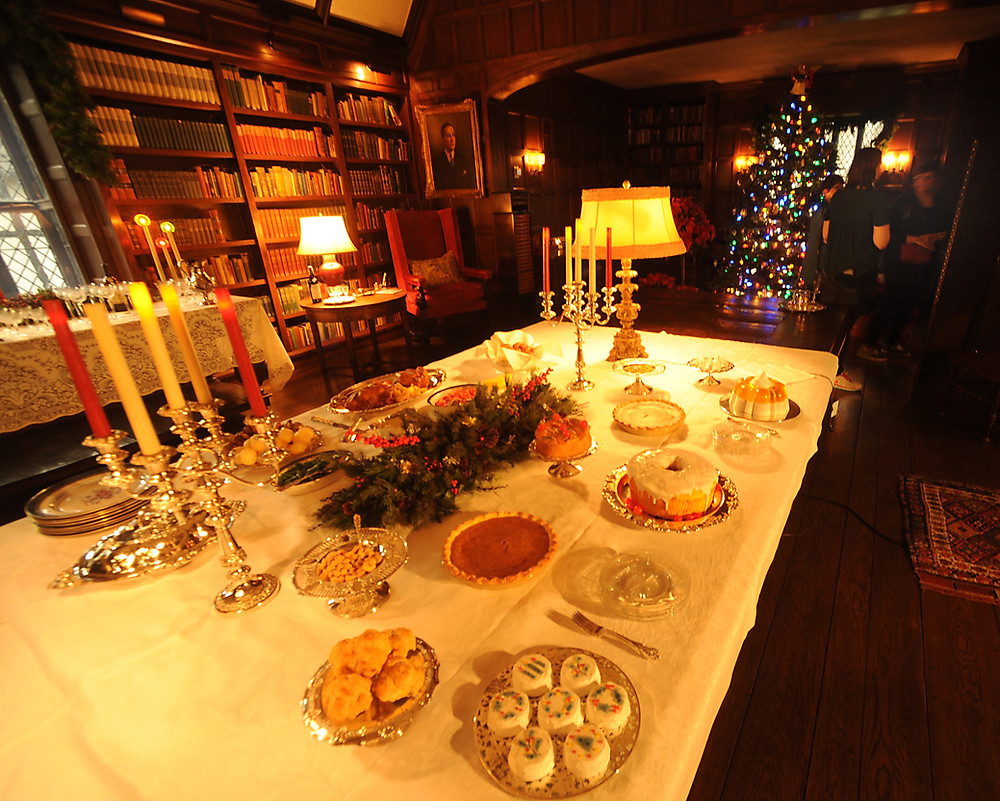 Photograph of a large table with candles and Christmas foods displayed for a party. Large cabinets of books and a Christmas tree are in the background.