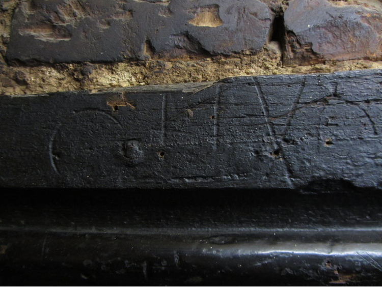 Detailed image of circular, vertical, and diagional marks carved into a section of wood.