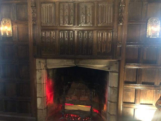 A wood panelled wall with carved designs surrounds a stone masonry fireplace with faux wood logs and red lights to simulate the look of fire.