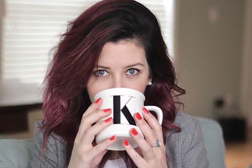 Hair stylist drinking coffee looking over the edge of the mug at the viewer.
