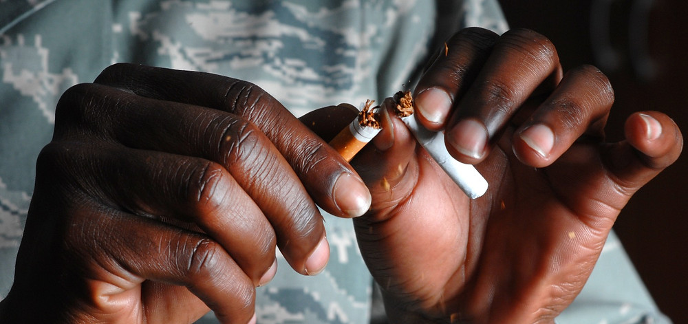 Man's hands breaking cigarette