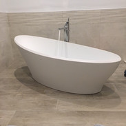Free standing bath with buried pipework.