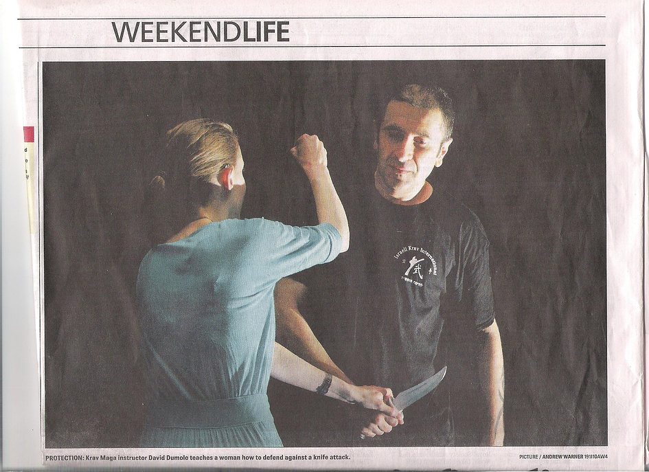 photo of David Dumolo teaching knife defense to a woman