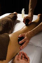 massage du mollet et de la cuisse lors d'un massage aux pierres chaudes