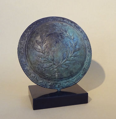 bronze shield with olive wreath and Greek meander design