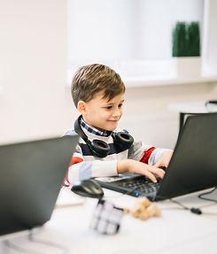 Baiat care se uita in monitor la cursuri online de informatica pentru copii
