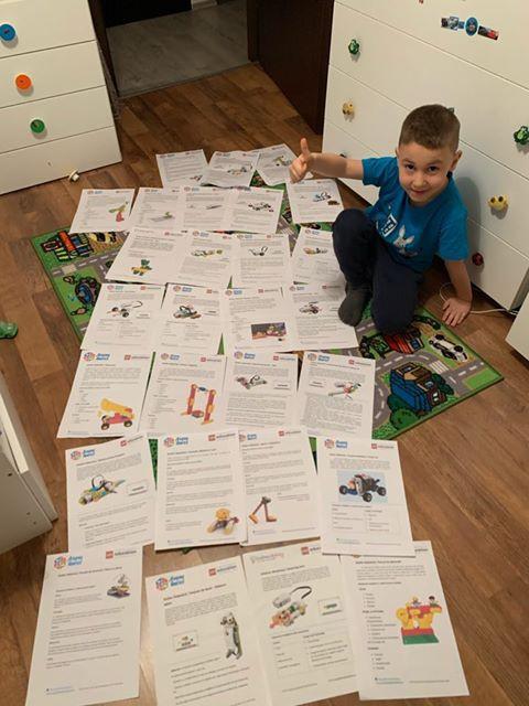 Copil pasionat de cursurile de Robotica Lego care isi afiseaya colectia de fise