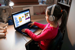 Fetita care participa la cursuri online pentru copii si programeaza in programul Scratch