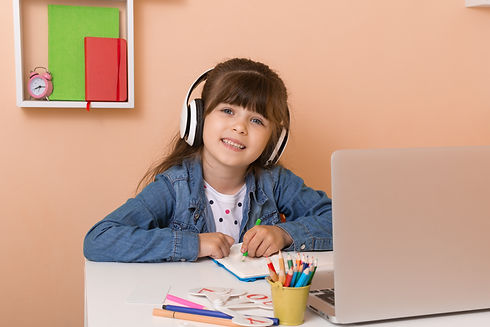 Kid girl with headphones using laptop at