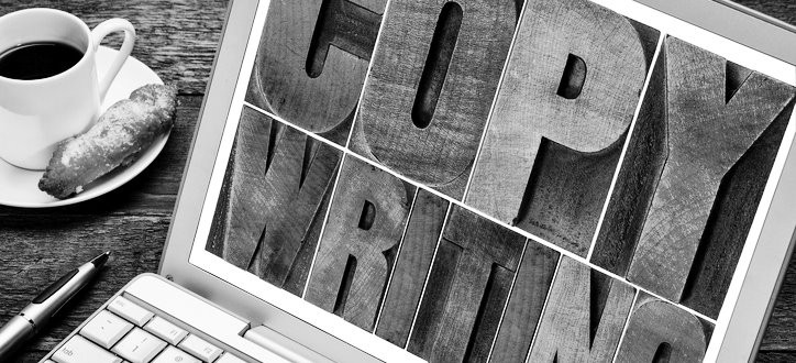 Black and white picture of a laptop screen showing wooden printing press letters spelling out Copywrighting