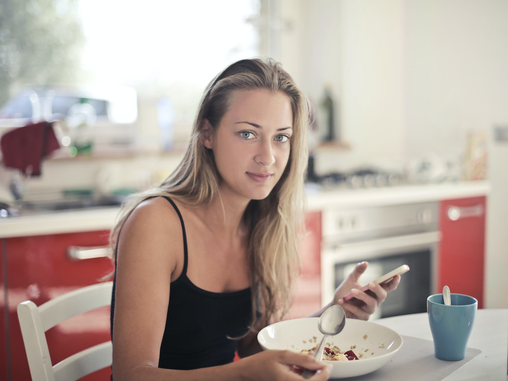 Woman eating and scrolling on her phone