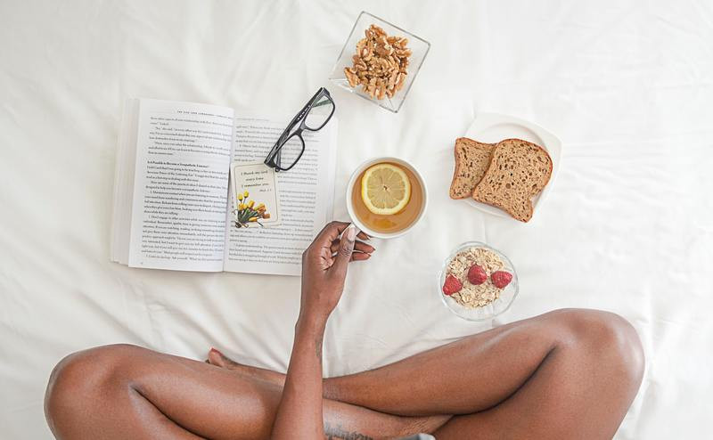 Woman sat on bed with healthy foods