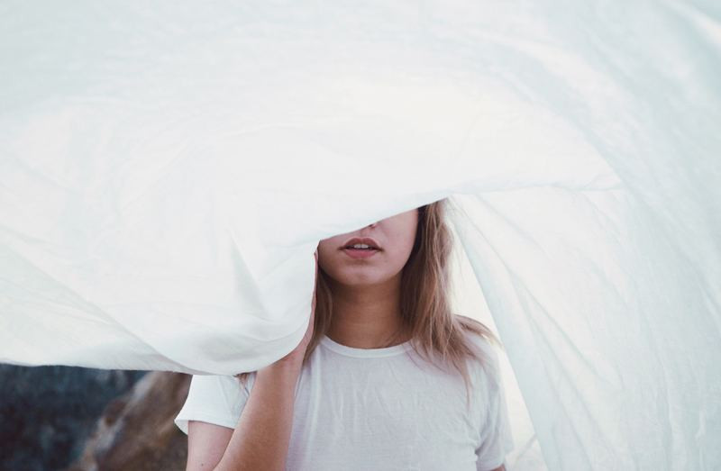 Woman under white sheet