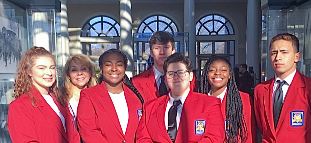 Vicky Pate is in a photo with multiple students in red jackets in Washington, D.C.
