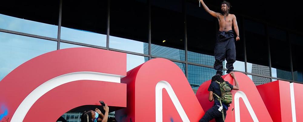 Mies heiluttaa BlackLivesMatter -lippua seisten CNN:n logon päällä