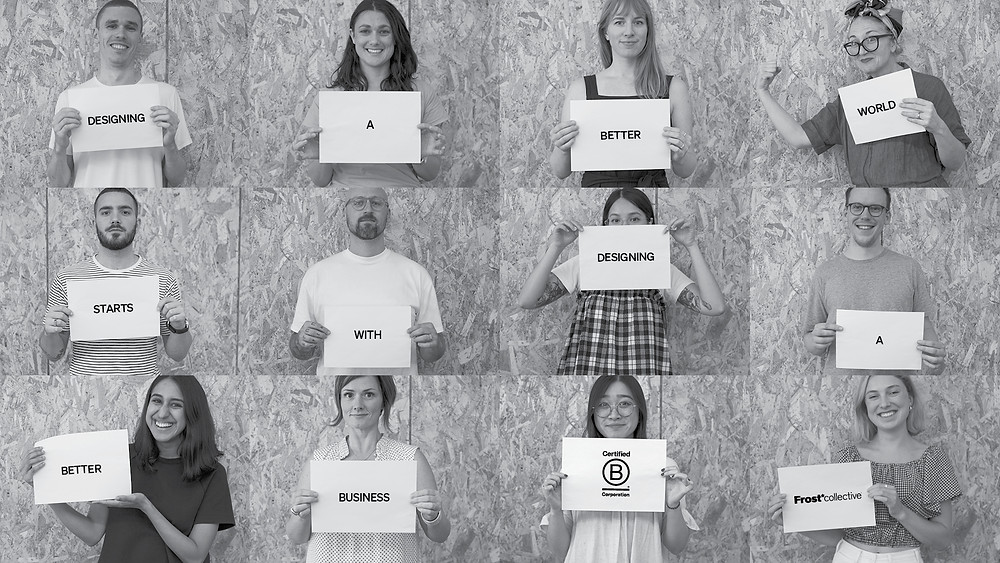 The Frost*collective team hold signs that say 'Designing a better world starts with designing a better business.'
