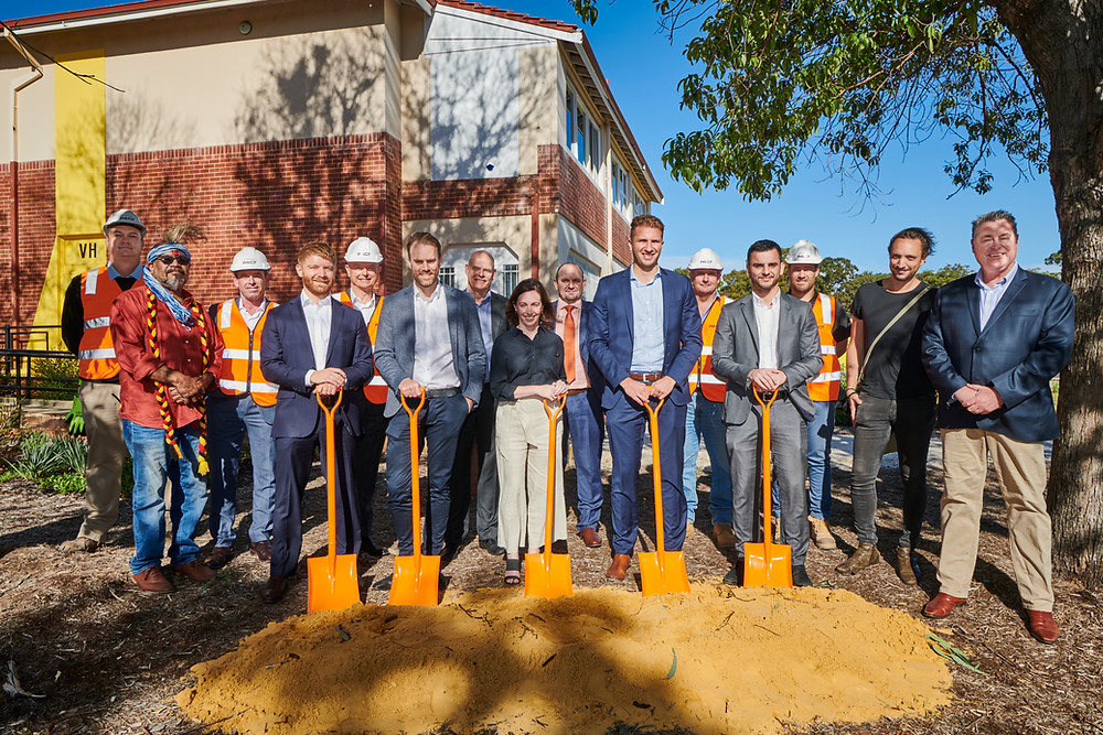 A group of people stand with shovels at a new construction site.