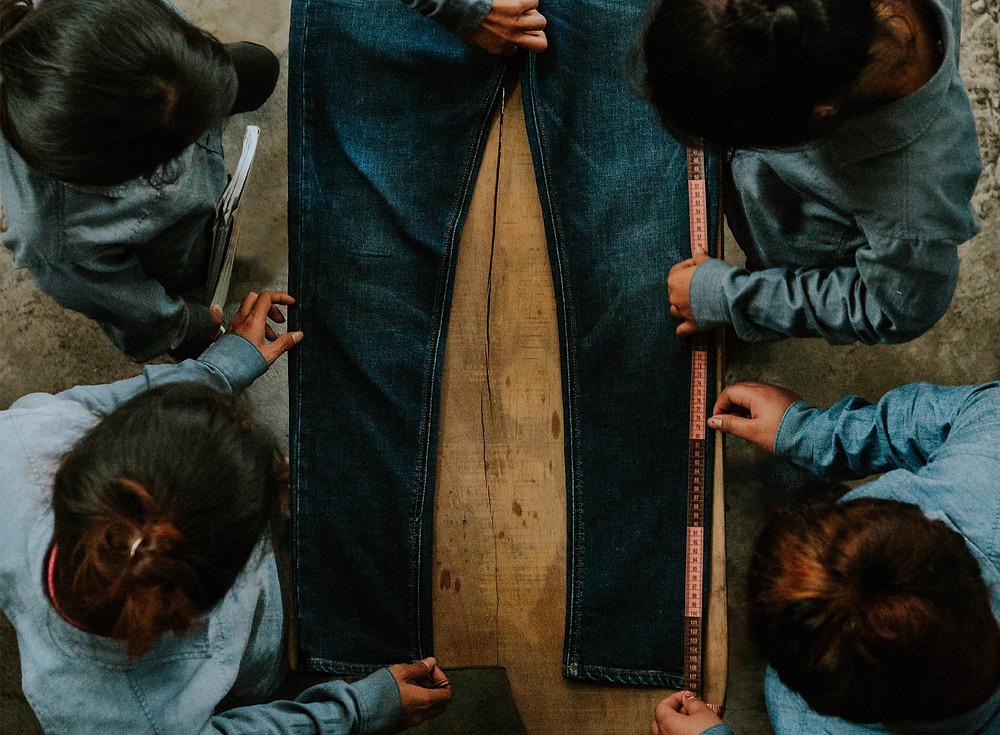 A group of workers put finishing touches on a pair of denim.