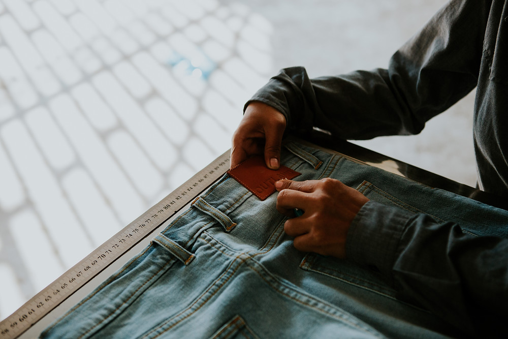 A worker sews the label onto the back of a pair of denim.