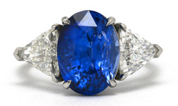 An oval sapphire ring with trillion cut accent diamonds.
